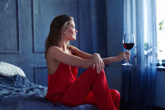 Задумчивая девушка при стекло красного вина смотря через окно Стоковое Изображение RF