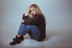 Задумчивая женщина в свитере сидя на поле стоковое изображение rf