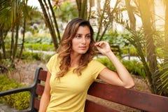 Задумчивая женщина сидя на скамейке в парке Стоковая Фотография