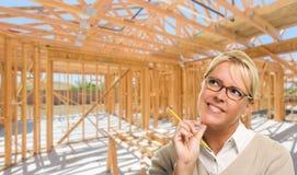 Задумчивая женщина с карандашем на месте внутри новой домашней конструкции f стоковая фотография rf