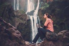 Задумчивая женщина с кружкой кофе около водопада Ouzoud в Марокко Стоковое Изображение