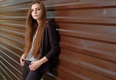 Задумчивая красивая девушка смотря камеру полагаясь назад против загородки металла с параллельными диапазонами Молодая девушка би стоковое изображение
