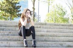 Задумчивая молодая женщина говоря телефоном и сидя на лестницах. стоковые фото