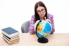 Задумчивая молодая студентка сидя с глобусом Стоковое фото RF