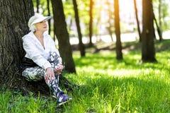 Задумчивая пожилая женщина ослабляя после тренировки в парке лета Стоковое Фото