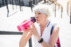 Задумчивая пожилая женщина отдыхая пока взбирающся вверх огромные лестницы города Стоковое Изображение RF