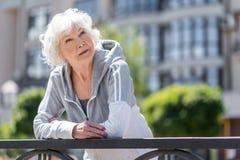 Задумчивая постаретая женщина отдыхая около загородки мостоваой стоковая фотография rf