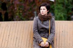 Задумчивая романтичная девушка положенная на деревянной загородке стоковая фотография rf