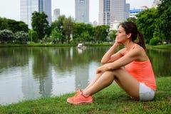 Задумчивая sporty женщина принимая остатки разминки стоковые фотографии rf