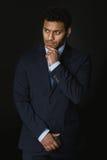 Задумчивое Афро-американское положение бизнесмена изолированное на черноте Стоковое фото RF