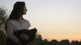 Задумчивое брюнет в белом платье с краном на взгляде рук на заходе солнца акции видеоматериалы