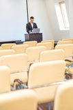 Задумчивое положение бизнесмена и компьтер-книжка использования в пустом конференц-зале Стоковые Изображения RF
