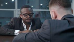 Задумчивые афро-американские и кавказские бизнесмены работая через бумаги и обсуждая финансовый отчет имея Стоковые Изображения RF