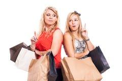 Задумчивые девушки ходя по магазинам и указывая вверх Стоковая Фотография