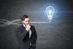 Задумчивые человек и электрическая лампочка с проводами Стоковые Изображения RF