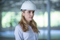 Задумчивый белокурый архитектор в трудной шляпе стоя и смотря прочь на работе Стоковая Фотография RF