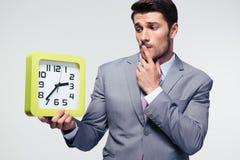 Задумчивый бизнесмен держа часы Стоковое Изображение RF