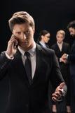 Задумчивый бизнесмен используя smartphone пока бизнесмены соединяясь позади Стоковые Изображения