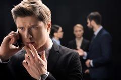 Задумчивый бизнесмен используя smartphone пока бизнесмены соединяясь позади Стоковая Фотография RF