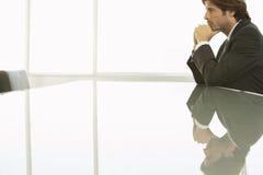 Задумчивый бизнесмен на столе переговоров Стоковые Фото