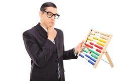 Задумчивый бизнесмен смотря абакус Стоковые Фото