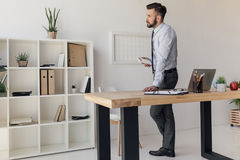 Задумчивый бизнесмен с калькулятором в руке стоя на таблице Стоковое Фото