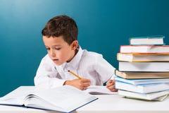 Задумчивый милый мальчик при домашняя работа сидя на таблице Стоковая Фотография