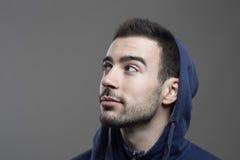 Задумчивый молодой бородатый человек смотря вверх нося голубую с капюшоном рубашку Стоковое Изображение RF