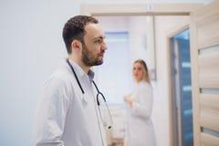 Задумчивый молодой доктор в белом пальто держа диагноз в больнице, заботя концепцию доктора Стоковое Изображение