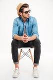 Задумчивый молодой человек сидя на стуле и думать Стоковое Изображение