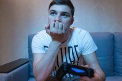 Задумчивый мужской gamer мечтая после играть видеоигры стоковое изображение