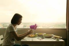 Задумчивый обедающий молодой женщины самостоятельно в комнате Стоковые Фото
