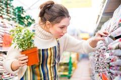 Задумчивый садовник женщины на покупках в магазине сада стоковое изображение rf