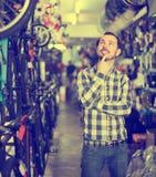 Задумчивый человек в магазине велосипеда выбирает для себя велосипед спорт Стоковые Изображения RF