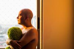 Задумчивый человек на окне Стоковое Фото