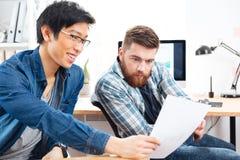 2 задумчивых люд сидя и работая с документами в офисе Стоковые Изображения RF