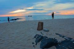 За утреннее время восхода солнца до, оператор рыболов на пляже Стоковые Фото