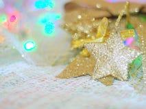 Звезда золота для украшений рождества на ткани knit и красочной предпосылке с концепцией торжества, рождества, Нового Года Стоковое фото RF