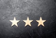 3 звезды на темной предпосылке Концепция оценки и оценки Оценка гостиницы, ресторана, передвижного применения Стоковое Изображение RF