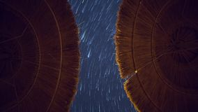 Звезды отстают трассировки на глубоком синем пейзаже предпосылки взгляда неба, симметричные зонтики следов пляжа на переднем план сток-видео