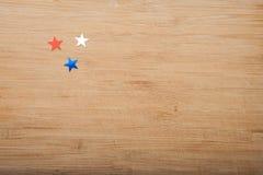 Звезды Confetti на деревянной предпосылке 4-ое июля, День независимости, карточка, приглашение в США сигнализирует цвета Взгляд о Стоковое Фото
