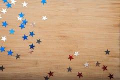Звезды Confetti на деревянной предпосылке 4-ое июля, День независимости, карточка, приглашение в США сигнализирует цвета Взгляд о Стоковые Изображения