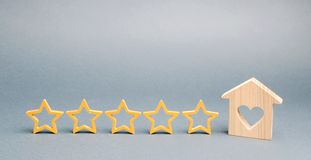 5 звезд и деревянного дом на серой предпосылке Концепция самого лучшего снабжения жилищем, роскошного класса VIP квартир Самое лу стоковые фото