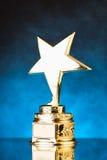 Звезда золота против голубой предпосылки частиц Стоковая Фотография RF