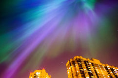 Звездная ночь северного сияния над городом и домами Стоковая Фотография