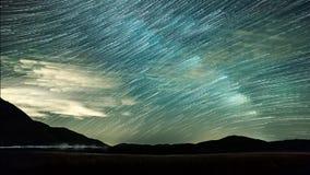 Звезды ночного неба Timelapse и следы звезды на предпосылке гор