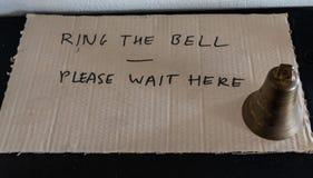 Звените колокол пожалуйста ждите здесь стоковые изображения rf