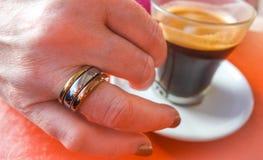Звените на ее пальце, эспрессо в чашке Стоковые Фотографии RF