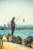 Звероловство рыболова морем Стоковая Фотография