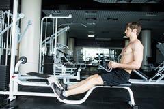 Зверский атлетический человек нагнетая вверх muscles на кроссовере Мышечный человек разрабатывая в спортзале делая тренировки гим стоковые фото